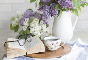 Amaranth flowers adorn a table with tea and a book published by Amaranth Press. Get help publishing your book.